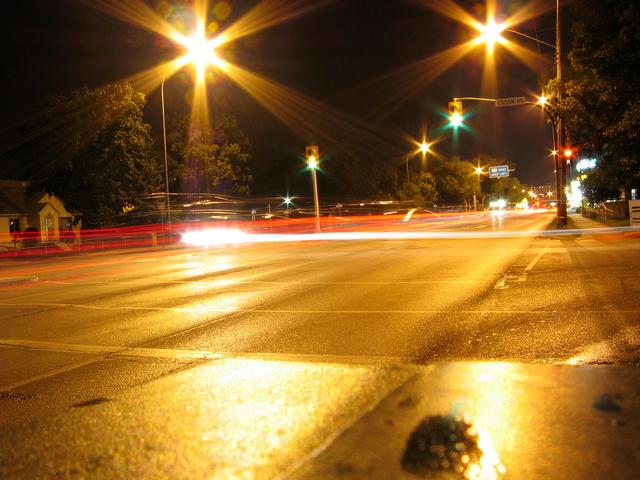 silnice v noci, světla od projíždějících automobilů semafory, na kterých je zelená
